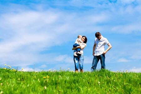 Young family standing on the meadow Stock Photo - 5832352