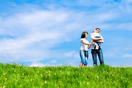 flowers field: Mother, father and baby on the meadow Stock Photo