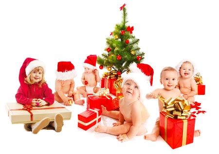 Group of Santa kids sitting beside Christmas tree photo