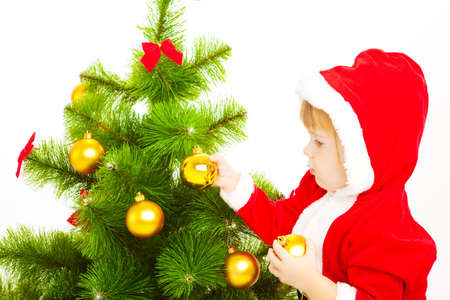 Baby in a red santa costume decorating Chritmas tree photo
