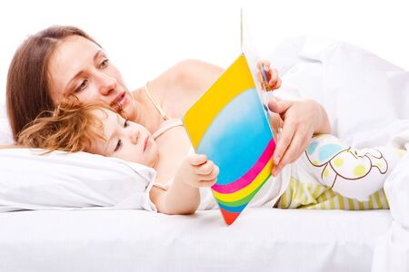 Mother reading her daughter a book in bed  photo