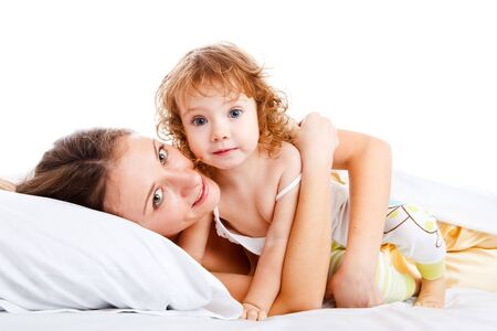 Beautiful mother and daughter lying in bed photo