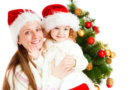 baby open present: Mother and little daughter sit near Christmas tree Stock Photo