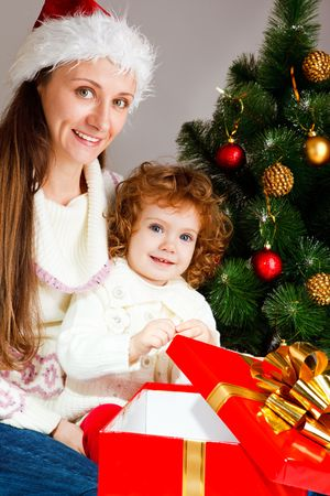 Mother and little daughter sit near Christmas tree with a present box Stock Photo - 5880483