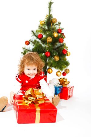 Cute happy toddler beside the Christmas tree with gifts under it photo