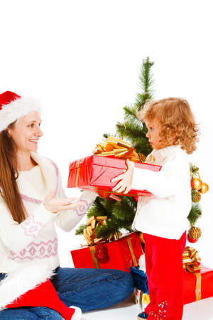 Cute little girl giving her mom  opening a Christmas present photo
