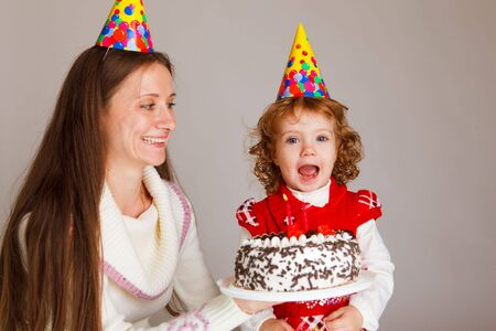 Mother giving her little daughter a birthday cake with two burning candles photo