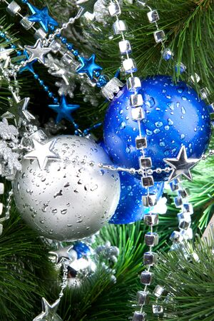 Blue and silver cristmas ball baubles with silver decoration on fir tree photo