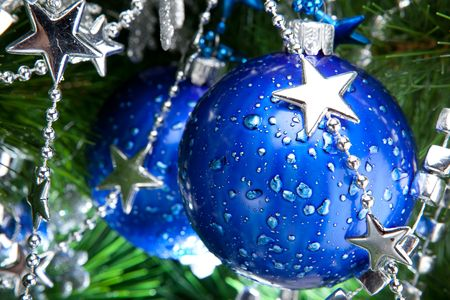 Blue cristmas ball baubles with silver decoration on fir tree photo