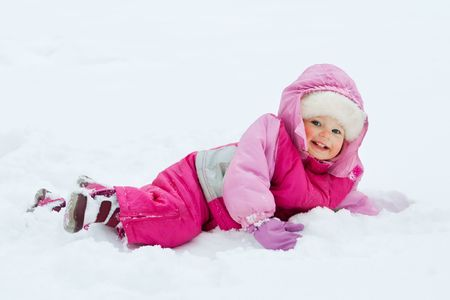Laughing baby girl lying in deep snow photo