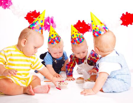 Babies in party hats celebrating first birthday Stock Photo