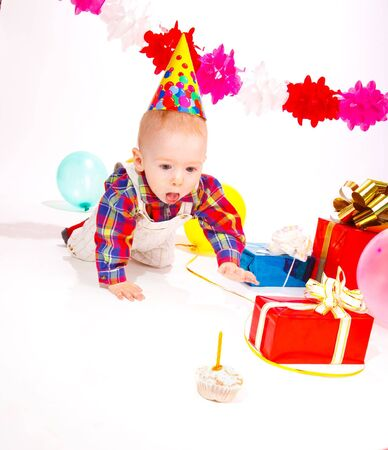 Baby in a party hat crawling to the birthday cake photo