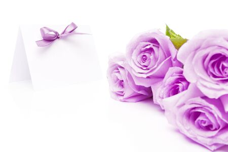 Invitation card in focus and a bunch of purple roses