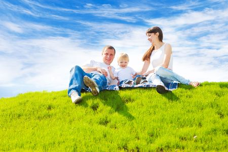 Young happy family sitting on the spring grass  Stock Photo
