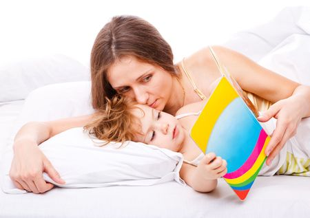 Mother and daughter lying in bed and reading a kids book photo