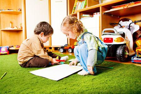 Preschool boy and girl drawing photo