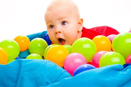 Portrait of a baby boy lying in basin with colorful balls photo