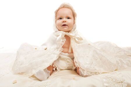 baptismal: Baby in baptismal clothing sitting on the satin blanket Stock Photo