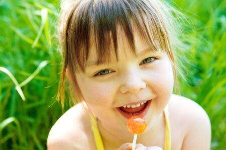 Cute preschool girl with lollipop, in park photo