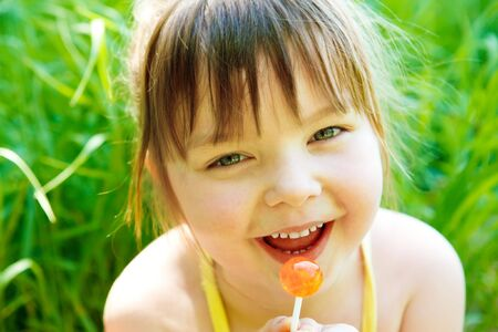 Cute preschool girl with lollipop, in park photo