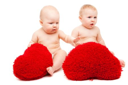 Two lovely babies playing with soft hearts Stock Photo - 6023597