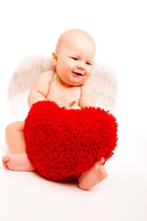 Cute happy valentine angel playing with red hearts photo