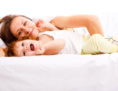 Beautiful mother and daughter lying in bed Stock Photo - 6061102