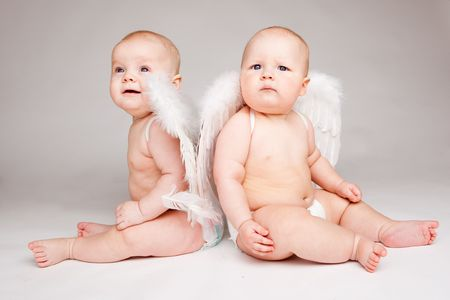 Two angelic baby friends in white wings and diapers photo