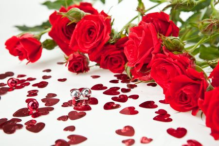 Red roses bouquet and hearts on white background photo