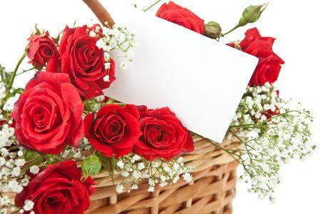 sobres para carta: Rosas rojas y la tarjeta de invitaci�n en blanco en la canasta de mimbre Foto de archivo