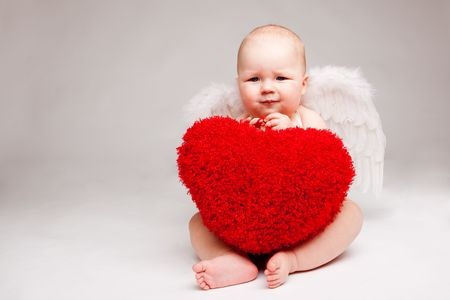 Cute happy valentine angel with red soft heart, over gray photo