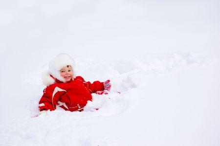 Laughing kid lying in the deep snow Zdjęcie Seryjne