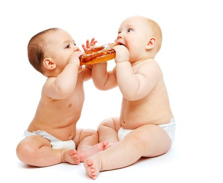Two lovely hungry babies eating a roll photo
