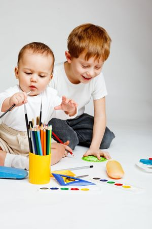 Little baby and preschool boy drawing, over gray Stock Photo - 6156522