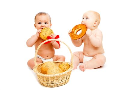 Two sweet babies in diapers eating buns Stock Photo - 6156523