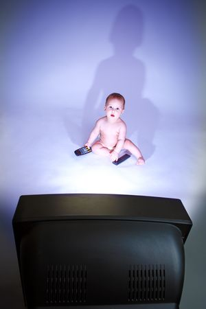 Baby with two remote controls, watching TV photo