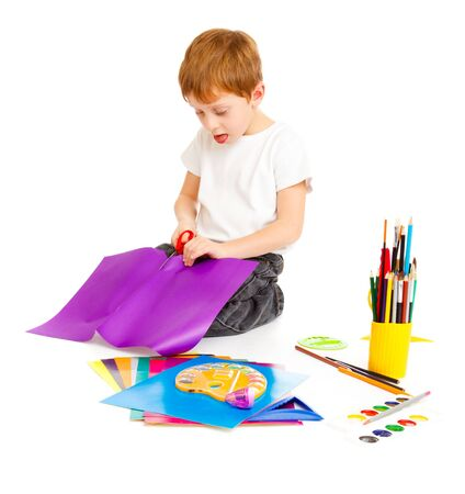 Preschool boy cutting paper with the scissors Imagens