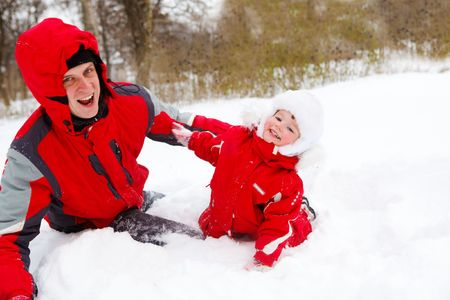 Happy father and baby having fun in winter park photo