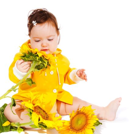 sweet baby girl: Dulce ni�a en amarillo mirando de girasoles Foto de archivo