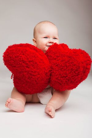 Cute happy valentine baby playing with red hearts photo