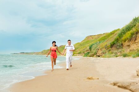 Happy young couple running at the beach photo
