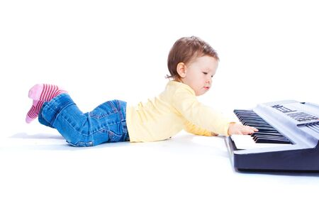 Adorable toddler lying and playing piano, isolated photo
