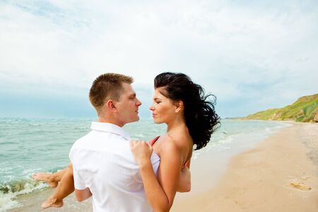 man carrying woman: Romantic couple enjoying their time together at the beach