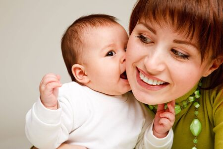 Closeup portrait of a sweet baby kissing  mother photo