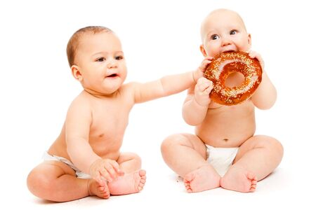 Two sweet babies in diapers eating bread photo