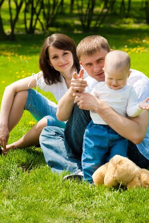 Family sitting on grass in the spring park photo