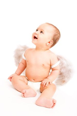 Happy angelic baby boy with white wings on, looking up photo