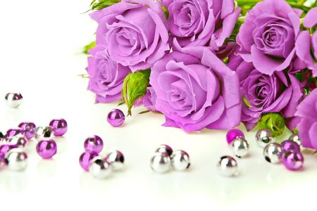 Purple roses bouquet and beads on white background
