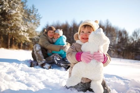 Toddler girl embracing bear toy and her parents looking at her behind photo