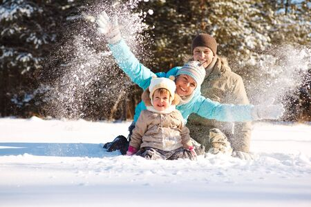 having fun: Attractive family having fun in a winter park Stock Photo